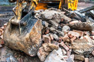close-up of excavator bucket loading rocks, stones, earth and concrete bricks